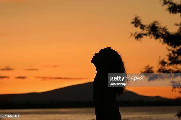 Silhouette of Girl Praying at Sunrise