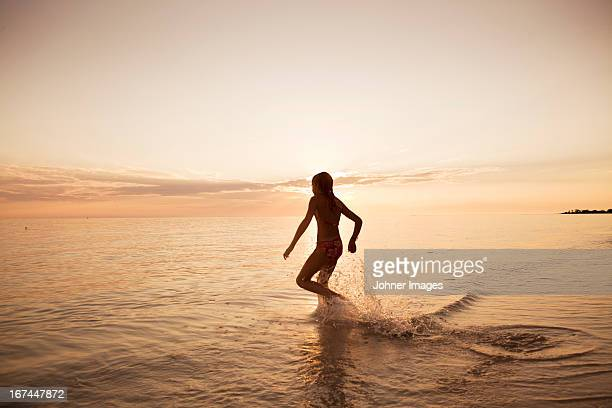 Silhouette of girl running into sea