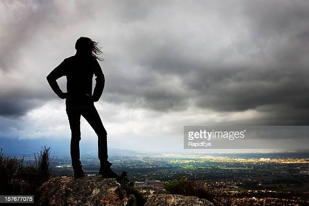 Silueta de chica bajo vehemente sky mirando hacia el área con luz natural