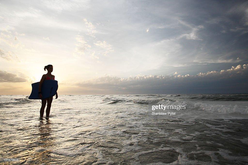 Silhouette of girl with bodyboard in sea : Stock Photo