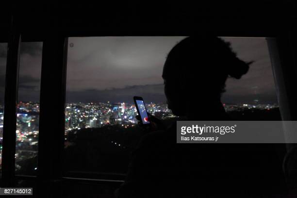 Silhouette of girl with smartphone in hand, city lights in the background