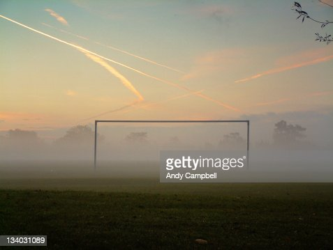 Silhouette of goalpost on misty football pitch