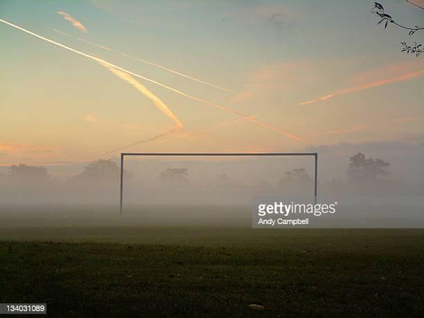 Silhouette of goalpost on misty football pitch