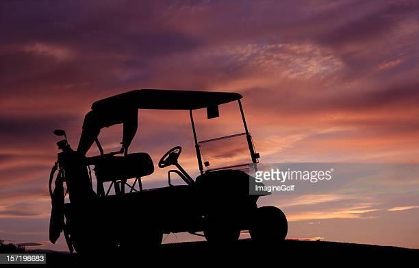 Silhouette eines Golfwagens vor orange und Lila Sonnenuntergang