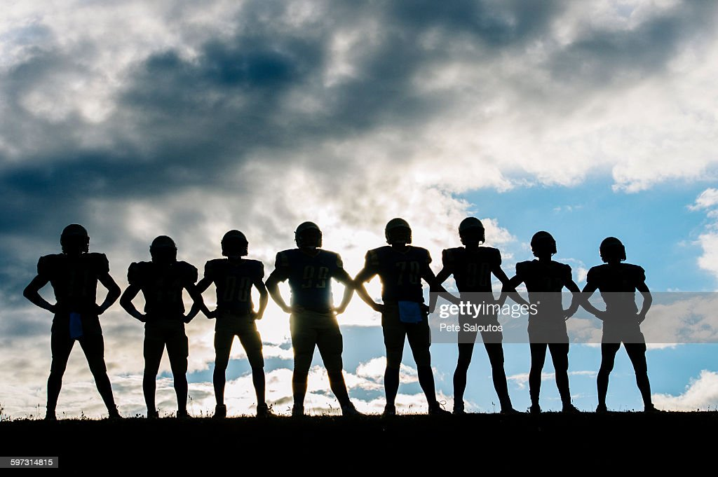 Silhouette of group of young american football players, standing in row, hands on hips