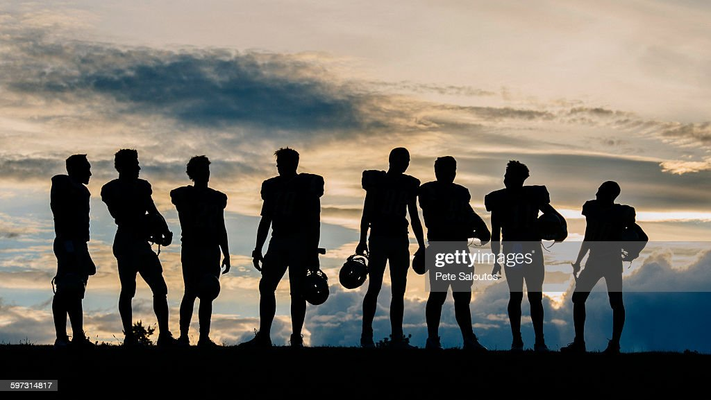 Silhouette of group of young american football players, standing in row