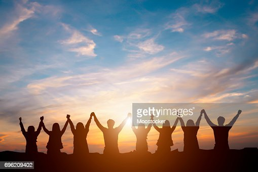 Silhouette of happy business team making high hands in sunset sky background for business teamwork concept : Stock Photo