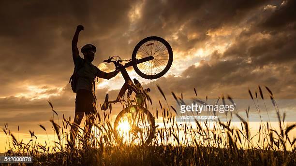 Silhouette de cycliste heureux pour atteindre le sommet de la montagne