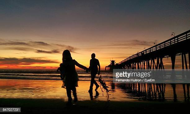 Silhouette Of Happy Family On Beach
