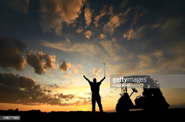Silhouette of happy golfer with arms raised and golf cart