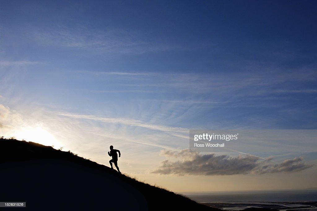 Silhouette of hiker running up hillside : Stock Photo