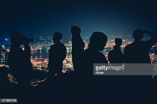 Silhouette of hikers on mountain top at night time