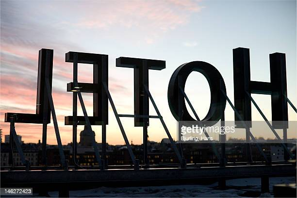 Silhouette of hotel sign against sky