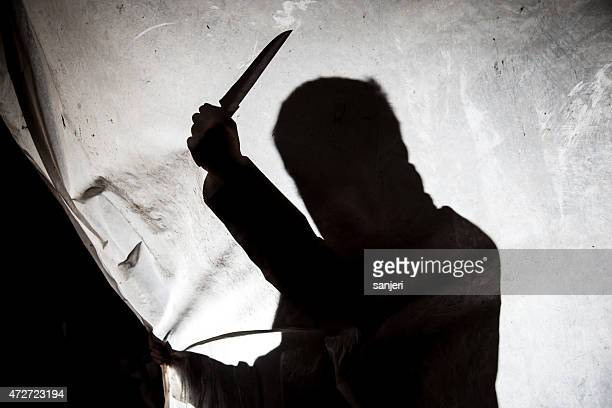 Silhouette of killer with knife in action