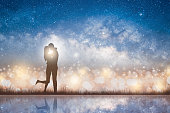 Silhouette of kissing couple love on the starry night sky