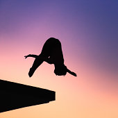 Silhouette of lady diver, diving from platform. Photographed at dusk against setting sun, colorful sky as background