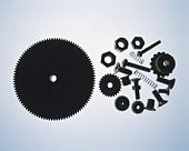 Silhouette of large gear and parts, high angle view, colored background
