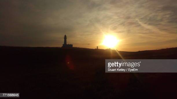 Silhouette Of Lighthouse On Field Against Sky At Sunset