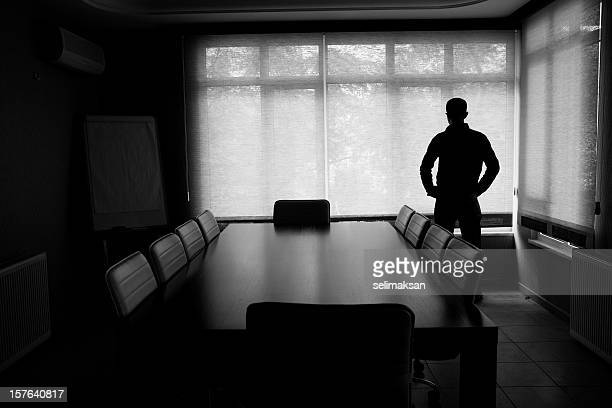 Silhouette Of Lonely Businessman Standing By Boardroom Table In Office