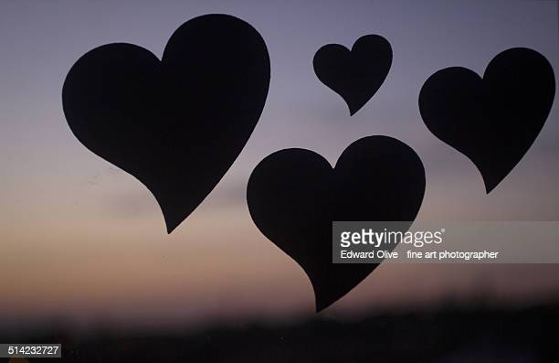 Silhouette of love hearts floating in sunset sky