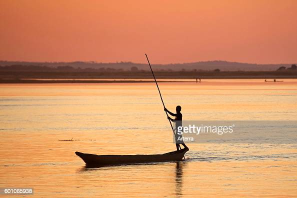 Silhouette of Malagasy fisherman punting pirogue / piragua / piraga with push pole on the Tsiribihina / Tsiribinha river at sunset in Menabe...