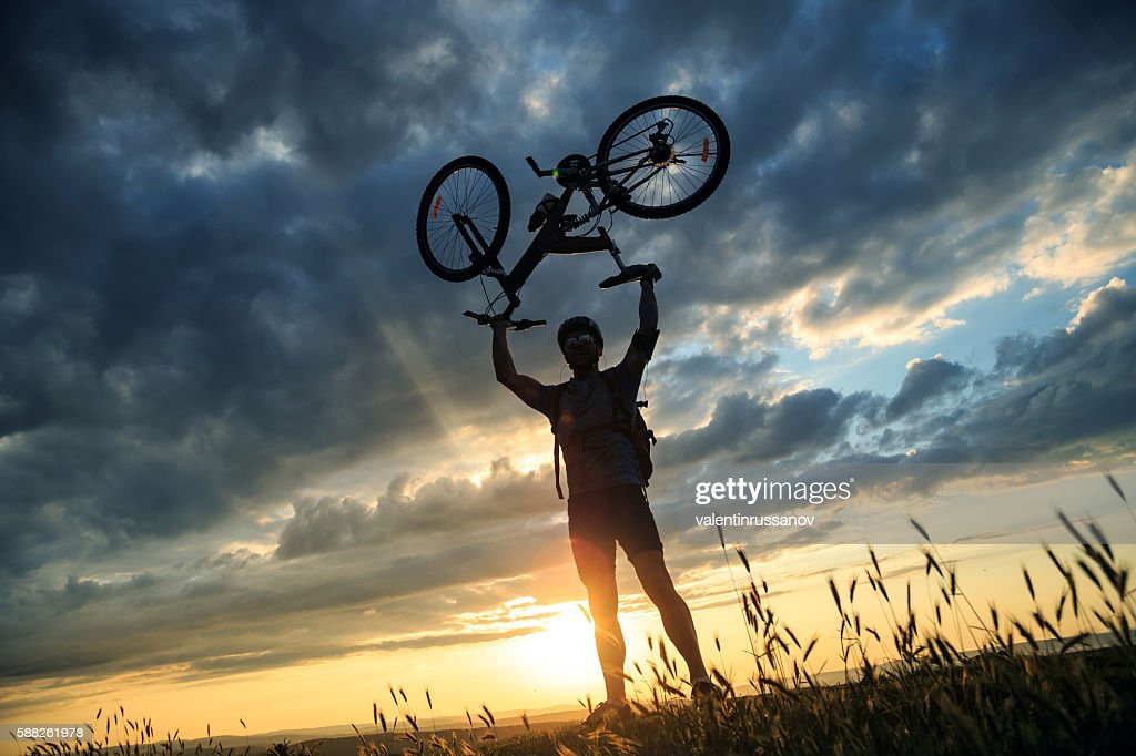 Silhouette of male mountainbiker at the top