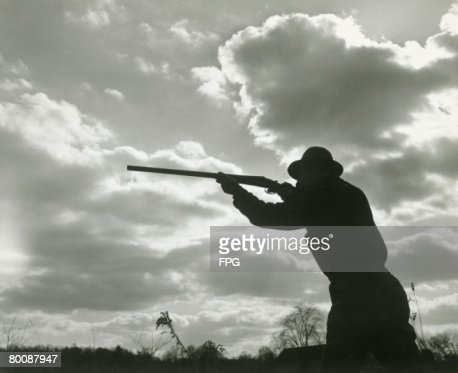 Silhouette Of Man Aiming Shotgun Outdoors Stock Photo ...