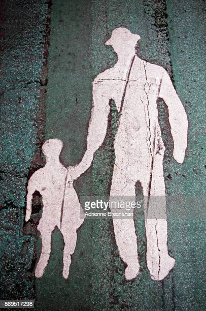 Silhouette of Man and Child Walking, Painted on the Street