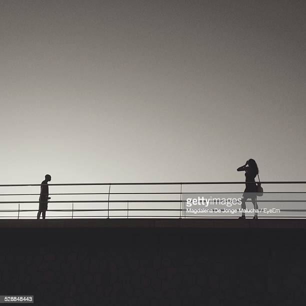 Silhouette Of Man And Woman On Bridge