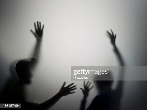 Silhouette of man and woman with raised hands