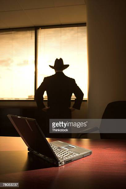 Silhouette of man at window with laptop on table