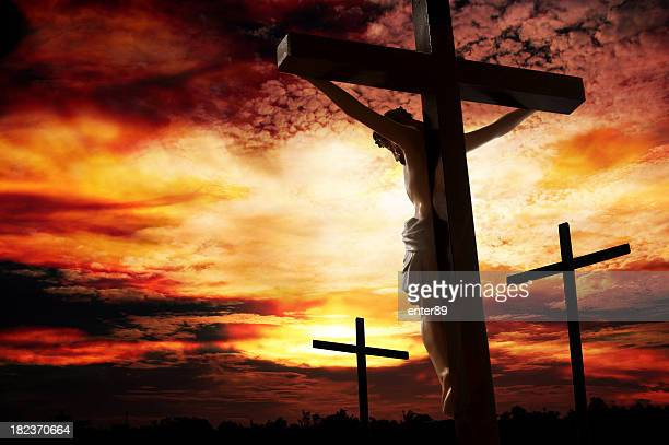 Silhouette of man being crucified against a vivid sunset