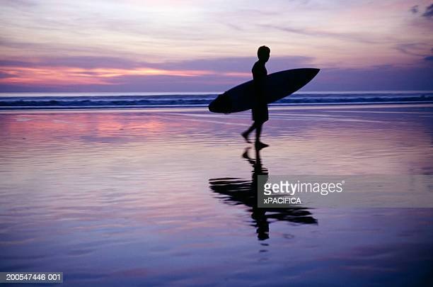 Silhouette of man carrying surfboard on beach at sunset