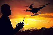 Silhouette of man controlling a drone at sunset.