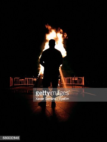 Silhouette Of Man Extinguishing Fire On Sidewalk