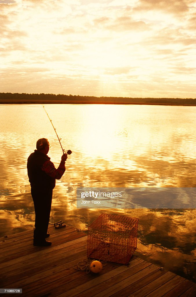 Silhouette of man fishing in lake on jetty : Stock Photo