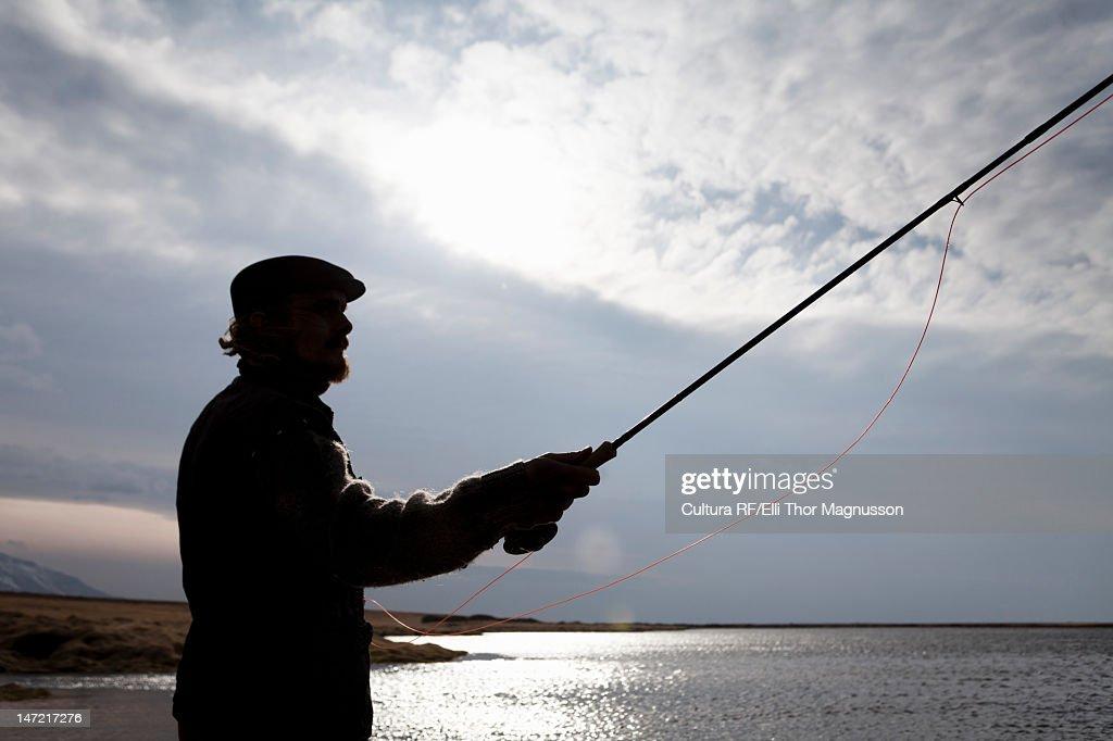 Silhouette of man fishing in still lake : Stock Photo