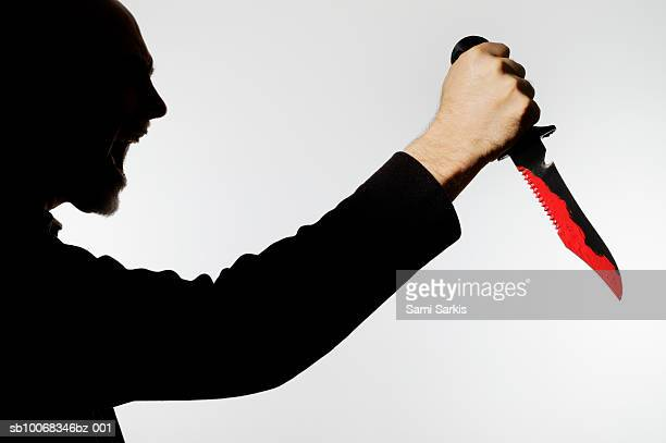 Silhouette of man holding blood stained dagger and yelling