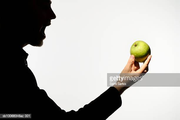 Silhouette of man holding green apple with mouth wide open