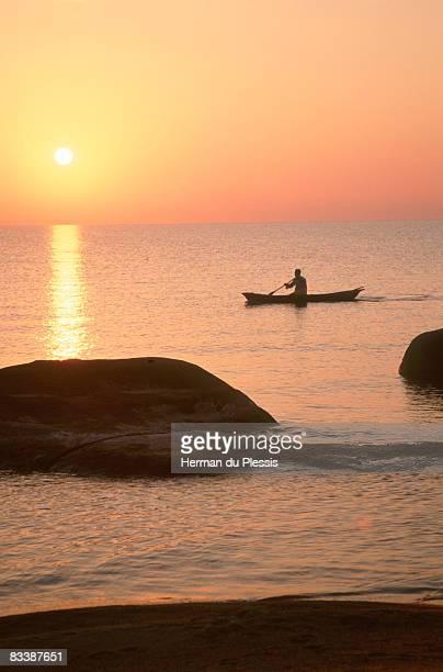 Silhouette of man in dug-out canoe against the setting sun, Senga Bay, Malawi