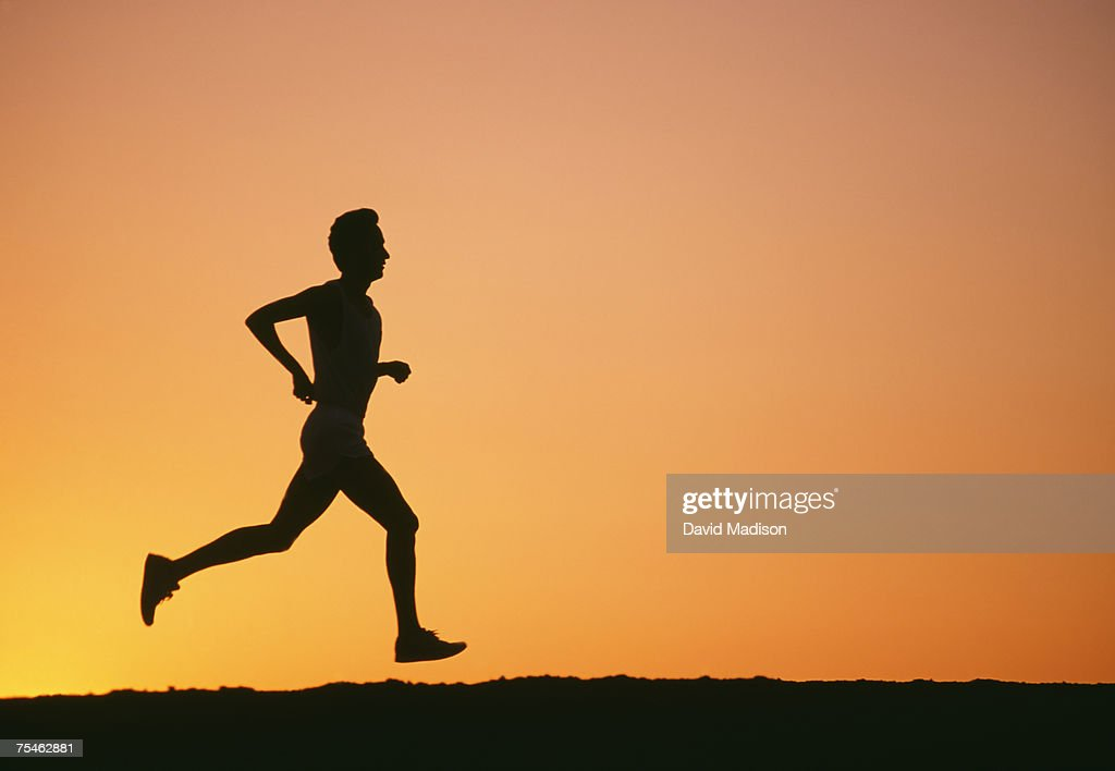 Silhouette of man jogging at sunset. California, USA. : Stock Photo
