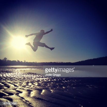 Silhouette of man jumping in air at sunset