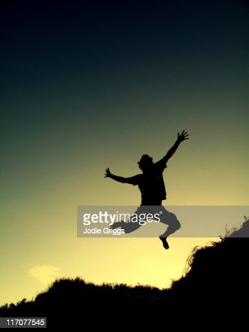 Silhouette of man jumping of sand dune : Stock Photo