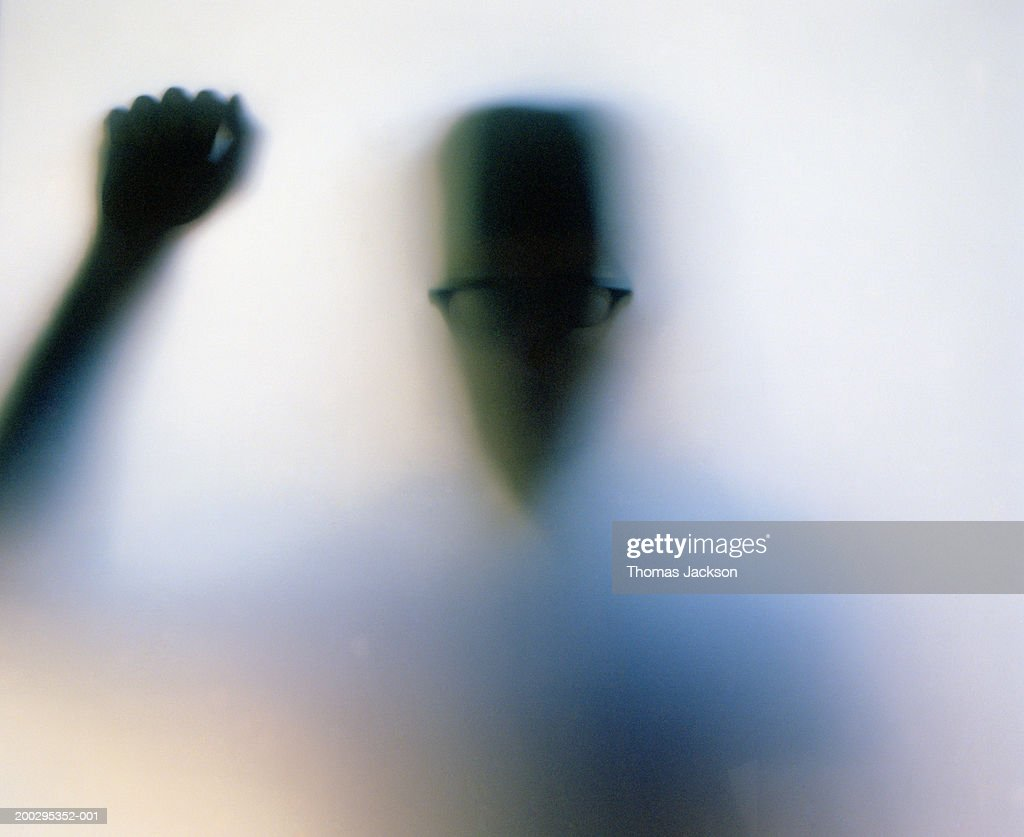 Silhouette of man knocking on frosted glass door (backlit)