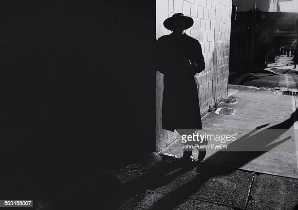 Silhouette Of Man Leaning Against Wall
