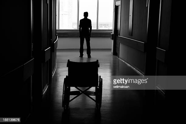 Silhouette of man leaving wheelchair in corridor of hospital