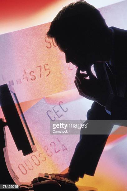 Silhouette of man looking at flat screen monitor with ticker tape