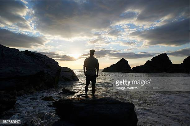 Silhouette of man looking out to sea