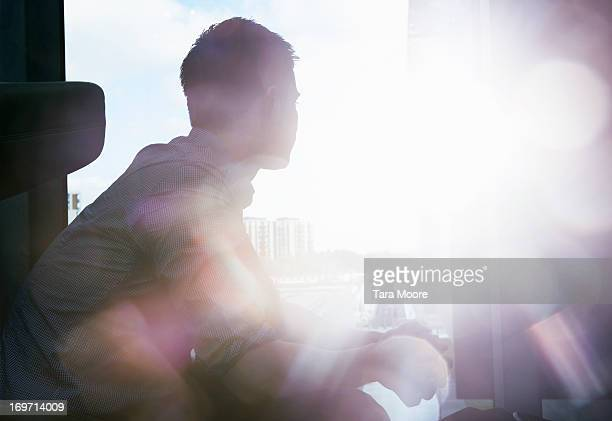 silhouette of man looking out window with flare