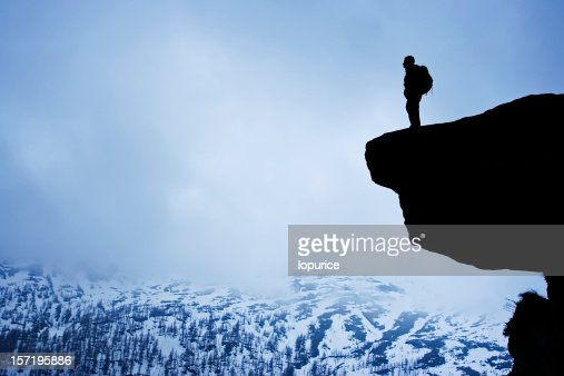 Silhouette of man on a hill overlooking snowy mountains
